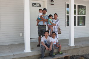 The Kay Reh family standing in front of their new home.