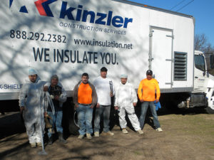 Installers from Kinzler Construction Services pose for a photo after insulating a home for a local homeless veteran.