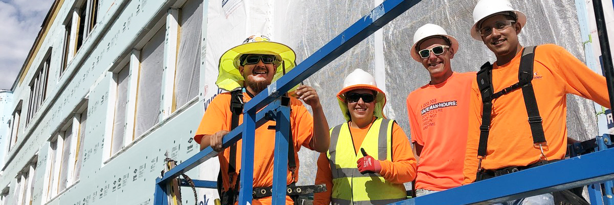 Kinzler installers in a boom lift smile for a photo on a Continuous Insulation job site.